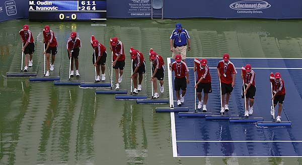 Balls boys work to clear the court of water after heavy rain suspended play between Ana Ivanovic of Serbia and Melanie Oudin of the US during their first round match of the 2009 Cincinnati Women's Open tennis tournament in Cincinnati.