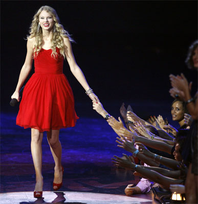 Fans show their support as Taylor Swift arrives onstage after being invited by Beyonce to finish her previously interrupted acceptance speech.