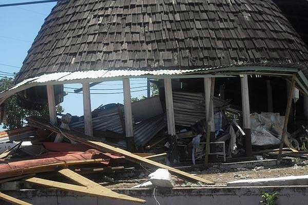 A fale sits in the middle of surrounding destruction.