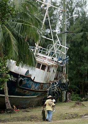 A man carrying his child walks past a boat that was washed ashore in Pago Pago Harbour, American Samoa.
