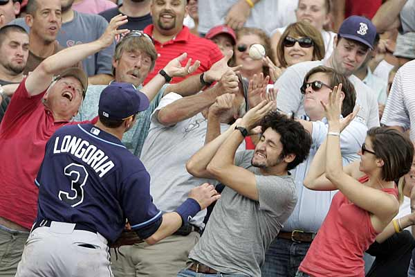 Tampa Bay Rays third baseman Evan Longoria watches as fans attempt to catch a fouled pop up hit by Boston Red Sox designated hitter David Ortiz during the eighth inning of the first game of their MLB American League baseball game doubleheader at Fenway Park in Boston, Massachusetts.