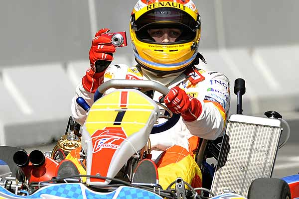 Spain's Formula One driver Fernando Alonso takes photos while driving a kart during an exhibition in Oviedo, northern Spain.