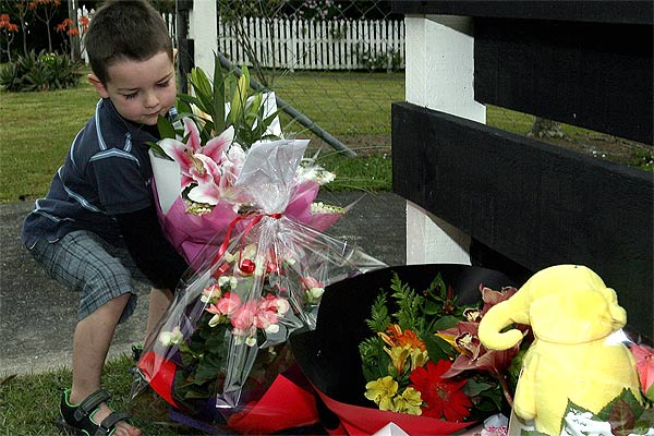 TRIBUTE: A boy lays a bouquet amid flowers and toys left outside the property which had belonged to the Symes family.