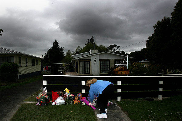 GRIEF: A woman places flowers outside the property belonging to the Symes family.