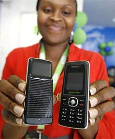 A Safaricom sales representative displays solar-charged mobile phone handsets in Nairobi.