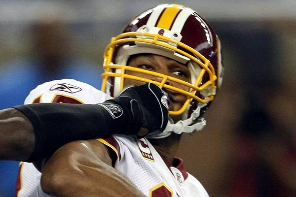 Washington Redskins quarterback Jason Campbell is face-masked by Detroit Lions defensive end Jason Hunter during the first half of their NFL football game in Detroit, Michigan.