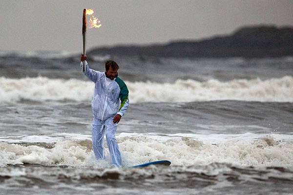 Surfer Raph Bruhwiler carries the Olympic Torch while coming ashore along Pacific Rim National Park just outside Tofino, British Columbia.