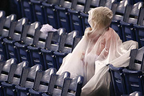 A spectator covers up during a rain storm before the start of Game 3 of the 2009 Major League Baseball World Series between the Philadelphia Phillies and the New York Yankees in Philadelphia.