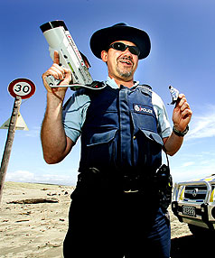 SWEET CHOICE: Ian Hamblyn plans to hand  out tickets or licorice chocolate  logs this summer, depending on the behaviour of drivers on Waitarere Beach.