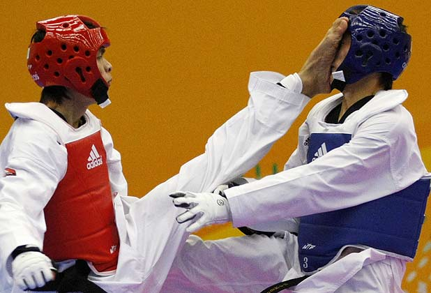 China's Chen Jiande (left) kicks Mongolia's Erdenebaatar Naranchimeg during their under 67 kg taekwondo match during the East Asian Games in Hong Kong.