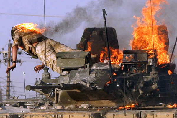 A British soldier on fire jumps from a burning tank