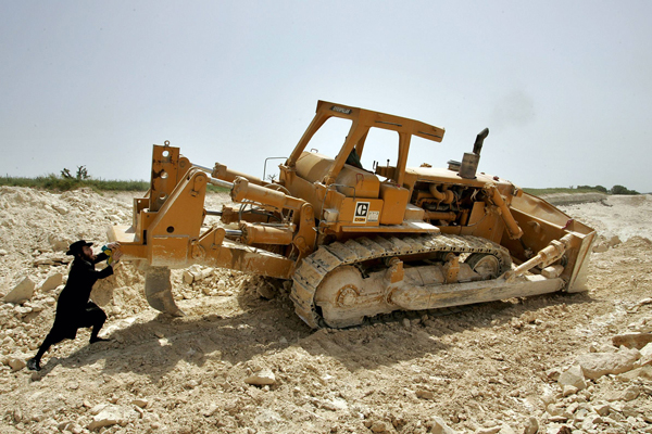 An ultra-Orthodox Jewish protester tries to push a bulldozer