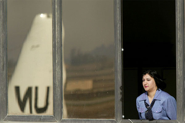 An Iraqi woman watches UN weapons inspectors leave Saddam Airport