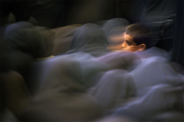 A boy sits among women during morning prayers in a mosque