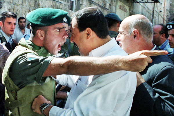 An Israeli policeman and a Palestinian scream at each other