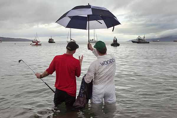 Swimmers impersonating golfer Tiger Woods and his caddy strike a pose in the waters of English Bay during the 90th annual Polar Bear Swim in Vancouver