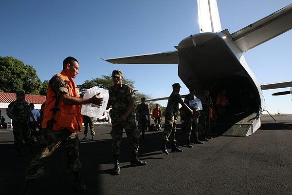 Members of Nicaragua's civil defence load a plane with boxes of humanitarian aid bound for Haiti at an air force base in Managua.