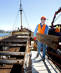 STRIPPED BACK: Wellington harbour ranger Grant Nalder with wood from the King Kong boat.