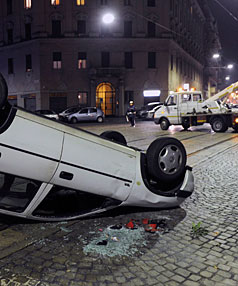 CLEANING UP: An overturned car lies on a street after a riot between North African and South American immigrants in downtown Milan.