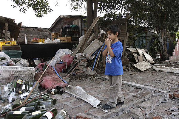 A boy stands amid the rubble of his home after a major earthquake in Santiago, Chile.