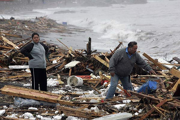 Residents inspect their home destroyed by the earthquake that generated waves flooding many towns to the north and south, in Pelluhue.