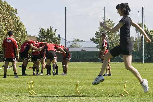 The Royal  New Zealand Ballet's Clytie Campbell does some speed work while the Crusaders rugby team train in the background at Christchurch's Rugby Park.