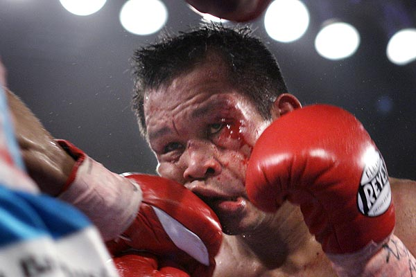 Bantamweight boxer Gerry Penalosa (right) of the Philippines takes a punch from Eric Morel of Puerto Rico at the Las Vegas Hilton in Las Vegas, Nevada.