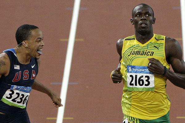 Wallace Spearmon of the US (left) sticks out his tongue beside Usain Bolt of Jamaica as they cross the finish line of their men's 200m semifinal at the Beijing 2008 Olympic Games.