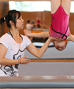 GUIDING HAND: Controversial Olympic medallist Dong Fangxiao helps out Charleis Kingston-White, 8, with her flips at Huntly.