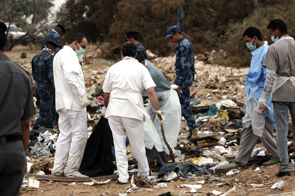 Rescue workers examine the debris of Afriqiyah airline flight 8U771 at Tripoli airport May 12, 2010.