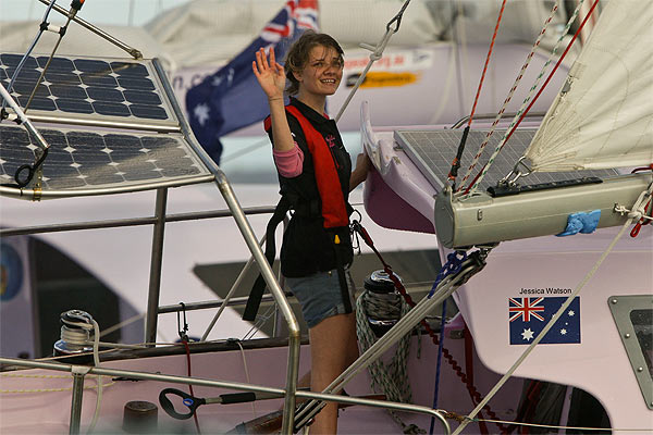 Jessica Watson waves as she sails her yacht Ella's Pink Lady into Sydney harbour.