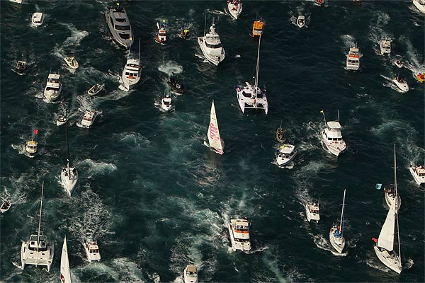 A flotilla of boats flanks teen sailor Jessica Watson as she enters Sydney harbour.