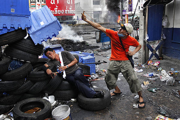 """An anti-government """"red shirt"""" supporter aims his slingshot at army soldiers, as his intoxicated comrade lies against a barricade made out of tires, at Rama IV Street in Bangkok."""