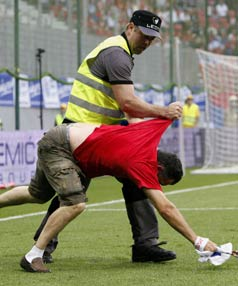 BAD REACTION: A Serbian supporter is scragged by a security guard after invading the pitch during his team's loss to the All Whites.