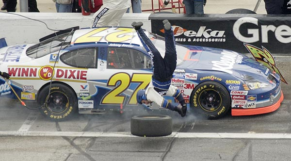 Pit crew worker Patrick Shafer, a front tyre changer for the number 27 Kleenex/Winn Dixie Pontiac, goes flying as the car makes a pit stop during running of the Hershey's Kisses 300 at the Daytona International Speedway in Daytona Beach, Florida February 14, 2004.