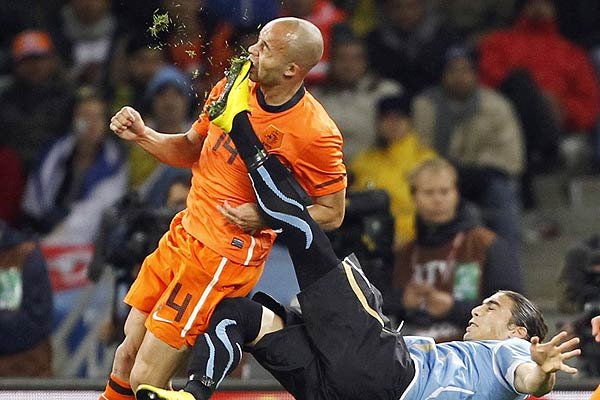 Netherlands' Demy de Zeeuw is kicked in the face by Uruguay's Martin Caceres during their 2010 World Cup semifinal football match at Green Point stadium in Cape Town.