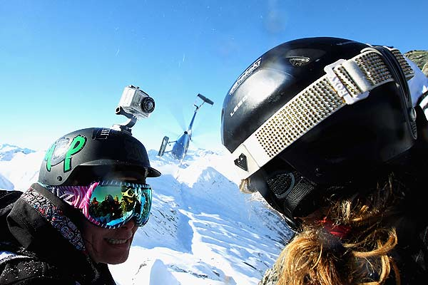 Sunny Prather of the USA and Elysia Gibb of New Zealand watch the helicopter depart (centre) as they wait at the summit during the Extreme Day of the World Heli Challenge at Mount Aspiring National Park.