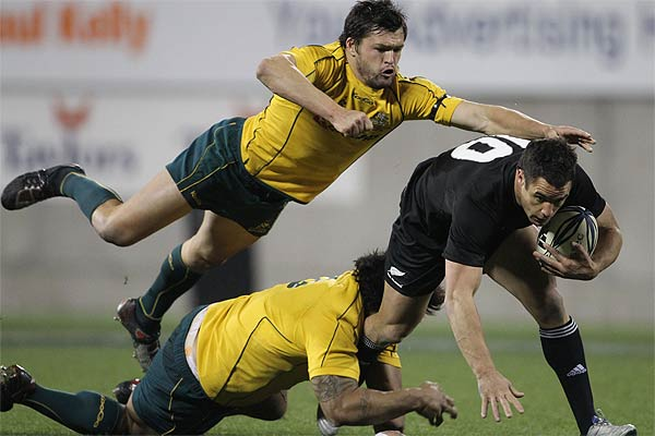All Black Daniel Carter attempts to step Adam Ashley-Cooper and Salesi Ma afu during the Bledisloe Cup rugby in Christchurch.
