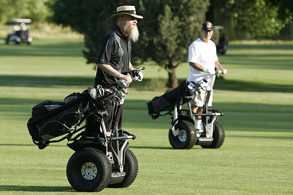 Marvin Hutchens and Jimmy Ray Henson ride down the fairway at Indian Tree golf course on Segway personal transports in Arvada, Colorado.