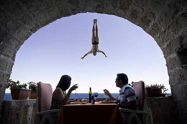 An Italian couple sits during lunch as Steve Black of Australia dives past their balcony in the lead up round four of the 2010 Red Bull Cliff Diving world series in Polignano a Mare.