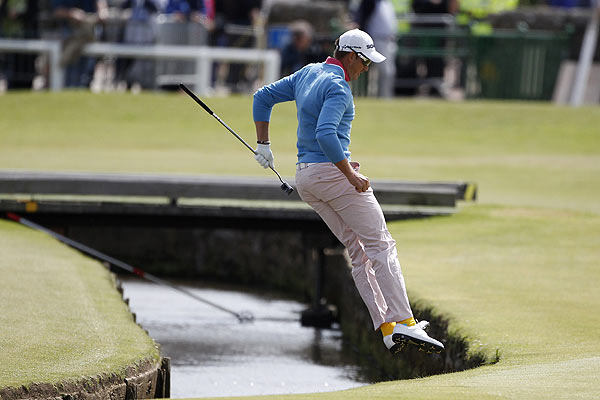 Sweden's Henrik Stenson jumps over the Swilcan Burn after chipping onto the first green during the final round of the British Open golf championship on the Old Course in St. Andrews.
