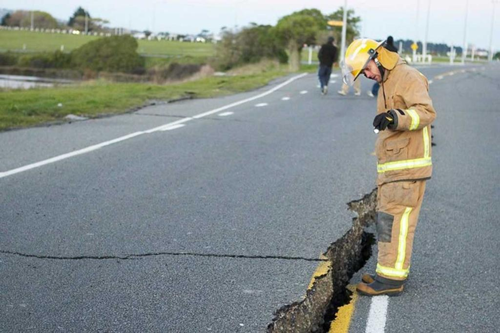 A firefighter inspects a road near New Brighton.