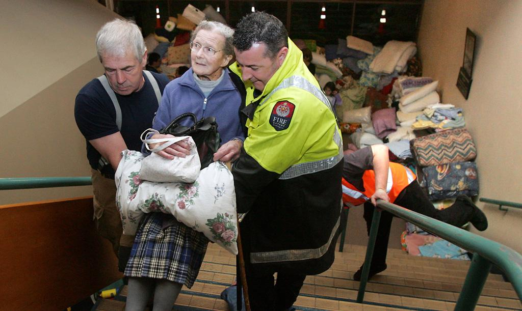 HELP AT HAND: Jean Sparks, 89, is lifted up the stairs at Addington Raceway by firefighters.