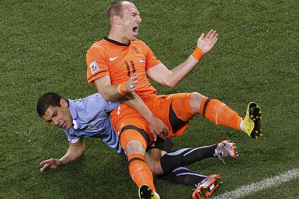 Uruguay's Maximiliano Pereira (left) tackles Netherlands' Arjen Robben during their 2010 World Cup semifinal football match at Green Point stadium in Cape Town.