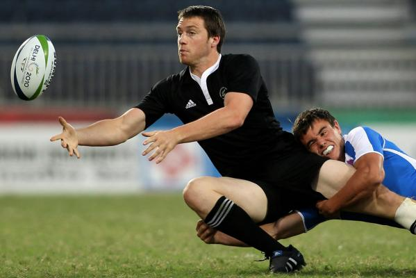 New Zealand's Ben Smith offloads the ball in the tackle of a Scottish player in the Pool A sevens match at the Delhi Commonwealth Games.