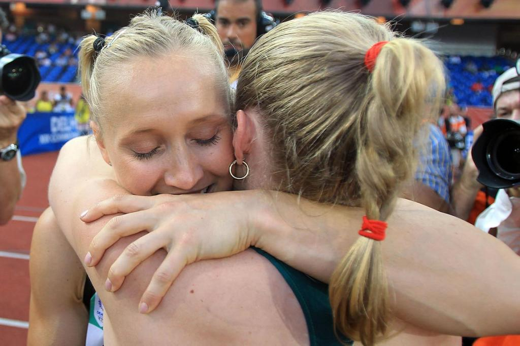 New Zealand's Andrea Miller (left) hugs winner Australia Sally Pearson after winning bronze in the women's 100m hurdles at the Commonwealth Games in Delhi.