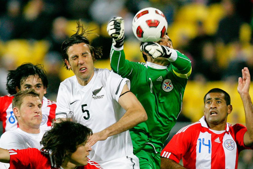 Ivan Vicelich goes up for the header while Paraguay's goalkeeper Justo Villar punches the ball away.