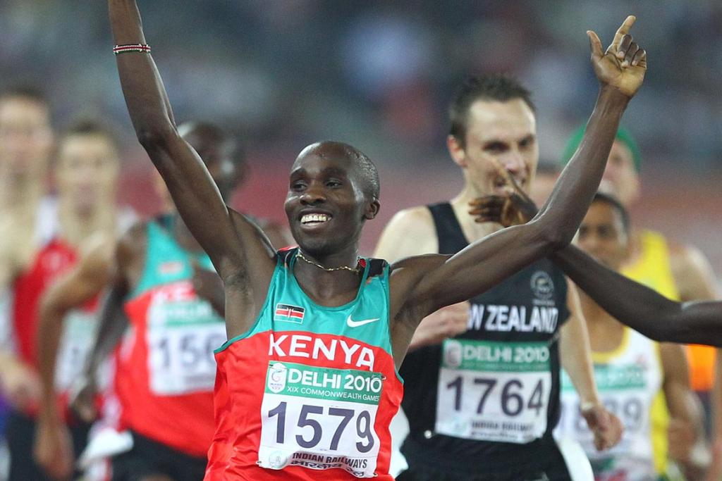 Kenya's Silas Kiplagat raises his arms aloft as he wins the men's 1500m final at the Delhi Commonwealth Games with New Zealand's Nick Willis behind in third place.