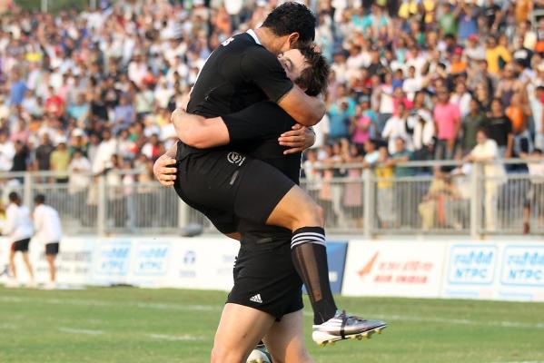 New Zealand's Kurt Baker (right) is hugged by teammate Sherwin Stowers after scoring the matchwinning try to beat Australia in the Sevens final at the Delhi Commonwealth Games.