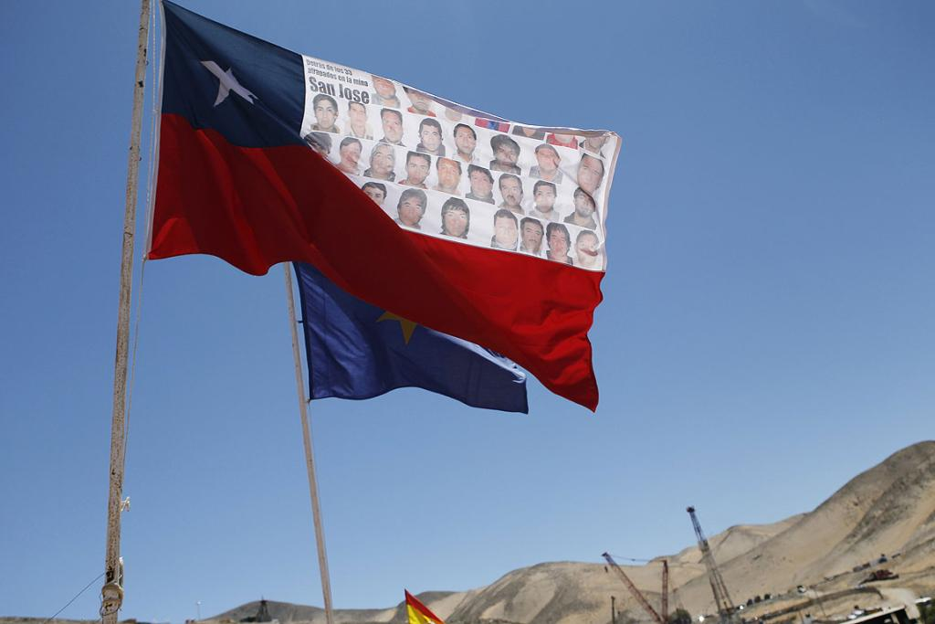 HOPE FLIES: A flag with the portraits of the 33 miners trapped inside the San Jose mine stands as the rescue operation continues in the distance.